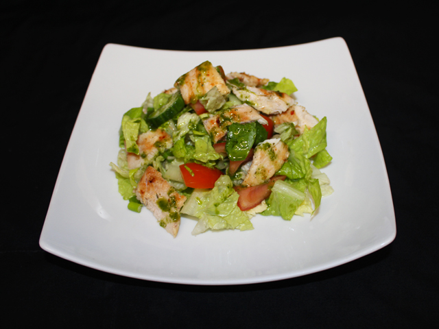 Strips of grilled chicken served on a bed of seasonal salad